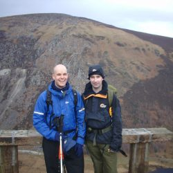 Mark Pollock and John ORegan stand before a mountainous landscape. Mark is wearing a blue jacket, holding two poles and John is wearing a navy jacket and hat.