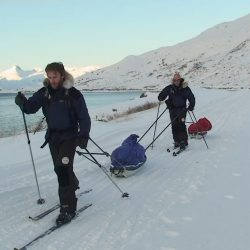 Simon ODonnell stands in front of Mark Pollock as they both ski along the snow pulling their pulks. (Mark is attached to Simons pulk.) Both are dressed in navy and black snow gear with fur hoods on their jackets. Mark wears dark glasses.