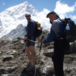 John ORegan and Mark Pollock hike up the side of a mountain as part of the Everest Marathon. John ORegan is to the left of the picture, wearing dark glasses, a white hat and blue and black shirt and shorts. Mark is to the right of the shot and wearing a navy hat, a blue and grey jacket and is carrying a black backpack. John and Mark are both holding onto either end of two poles as they climb.