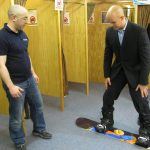 Mark Pollock, dressed in a suit, is standing on a snowboard smiling as he tries it out in a shop. A man to the left looks on.