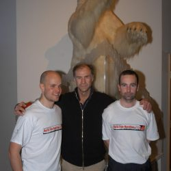 Mark Pollock, Sir Ranulph Fiennes and John ORegan stand in front of a stuffed polar bear. Mark and John both wear a white North Pole Marathon 2004 t-shirt. Ralph stands in between them with his hands on both of their shoulders, wearing a black zip up.