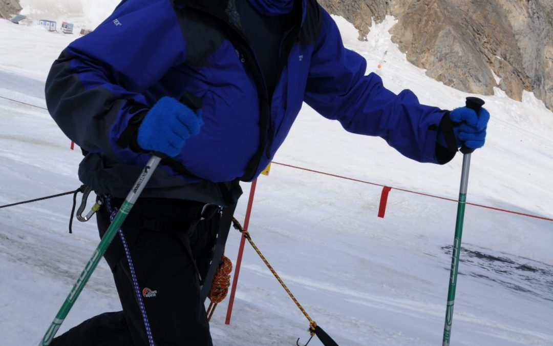 Mark Pollock, dressed in snow gear and dark glasses, skiing in snow