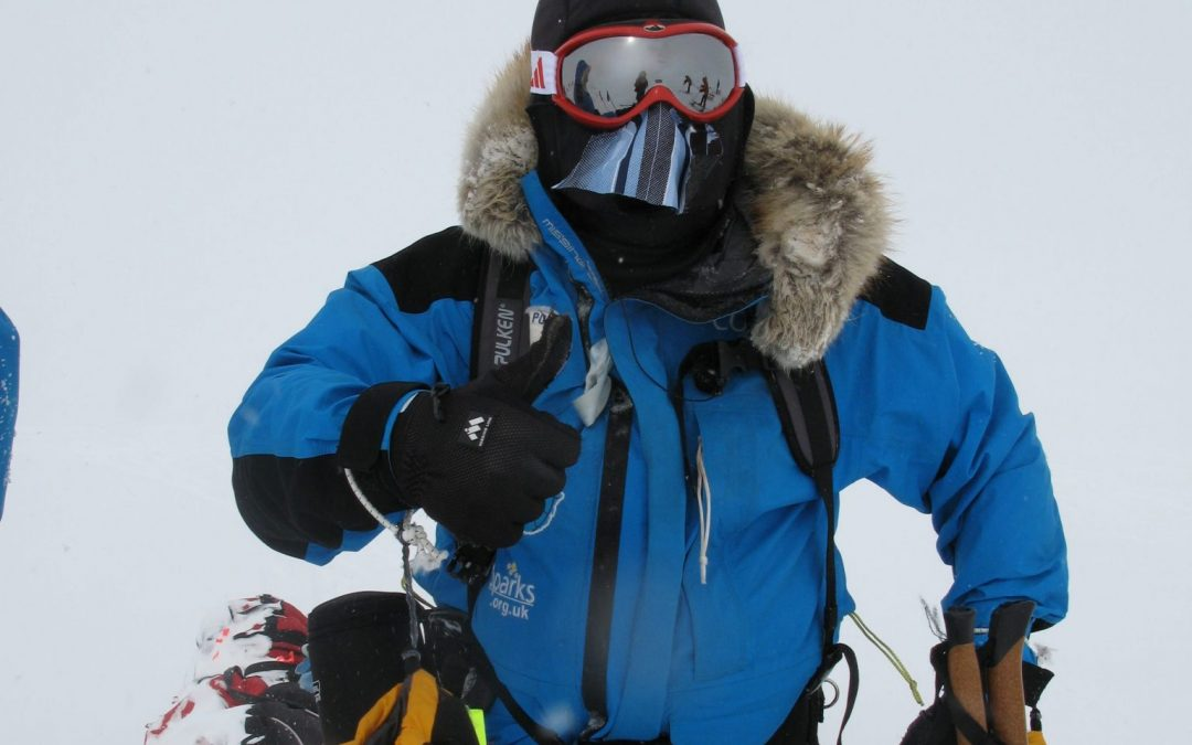 Mid-range shot of Mark Pollock standing in the snow in full snow gear, wearing balaclava, goggles, snow jacket with fur hood. One hand is in a thick yellow gloves while the other glove is removed so he can give a thumbs up gesture.