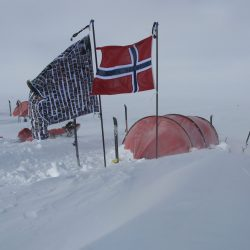 Marks South Pole Flag, which features all the faces of his supporters around the word, is pitched in the snow beside the Norwegian flag in front of a red tent.