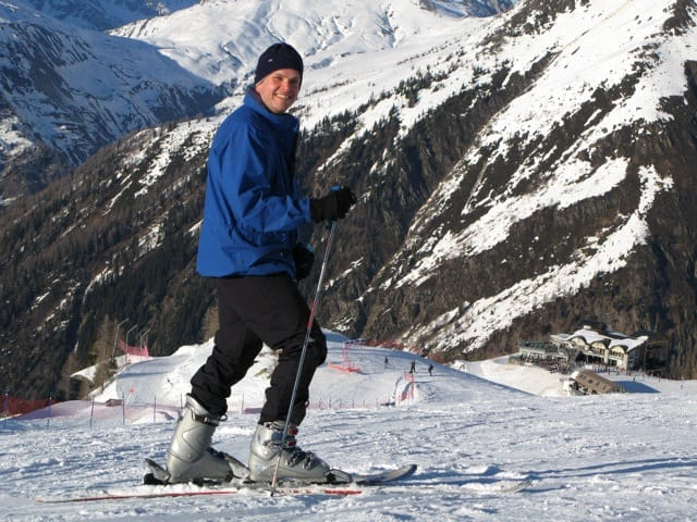 Mark Pollock dressed in a blue snow jacket, black hat, black trousers and silver ski boots as he poses on his skis and smiles at the camera while people ski in the distance behind him.